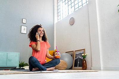 Smiling woman talking on mobile phone while holding juice jar at home - p300m2274623 by Giorgio Fochesato