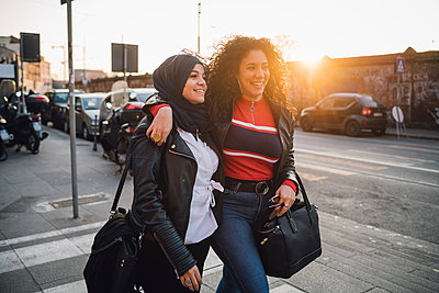 Young woman in hijab and best friend walking and talking in city at sunset - p429m2127834 by Eugenio Marongiu