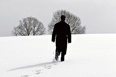 Man  walking in snow - p476m894099 by Ilona Wellmann