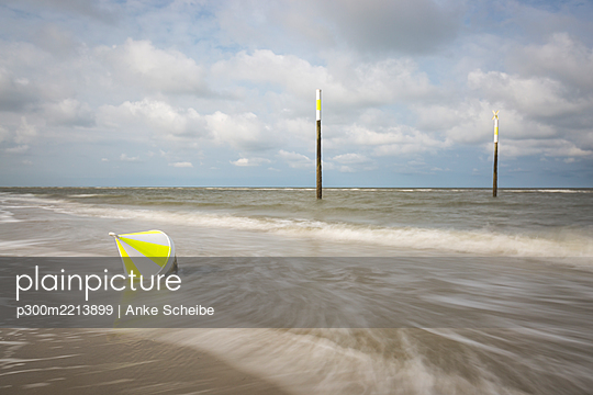 Buoy lying on sandy coastal beach of North Sea - p300m2213899 by Anke Scheibe