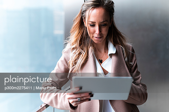 Smiling female professional using digital tablet while leaning on railing - p300m2275411 by Manu Prats