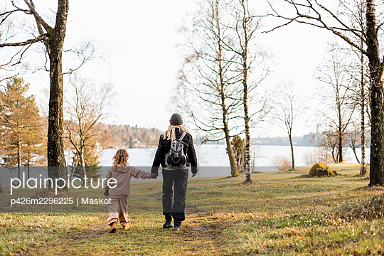Full length rear view of mother and daughter holding hands while walking towards lake - p426m2296225 by Maskot