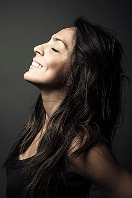 Profile portrait happy beautiful Latina woman smiling with head back - p1192m2066075 by Hero Images