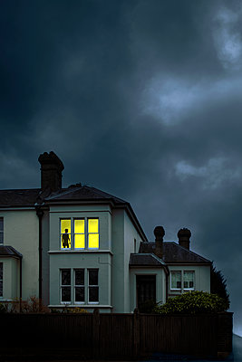 Terrace House with Silhouette at Lit Window  - p1248m2179124 by miguel sobreira