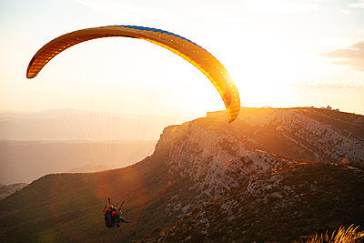 Spain, Silhouette of paraglider soaring high above the mountains at sunset - p300m2042852 by Oriol Castelló Arroyo