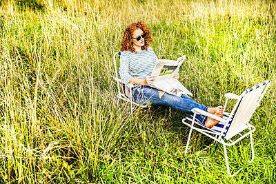 Young woman relaxing on a meadow reading newspaper - p300m2070555 by Jo Kirchherr