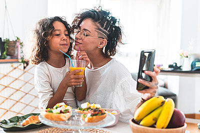Mother and daughter taking selfie during breakfast - p300m2242828 by Josu Acosta