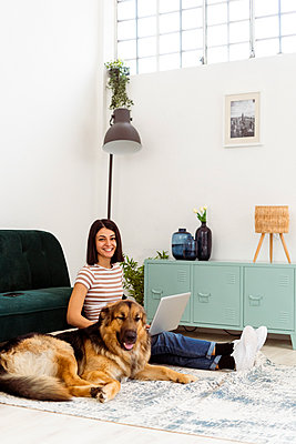 Smiling young woman with German shepherd sitting on carpet in living room - p300m2265285 by Giorgio Fochesato