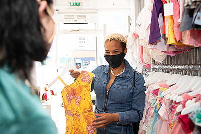 Lesbian woman wearing protective face mask showing dress to girlfriend at store - p300m2290787 by Pete Muller