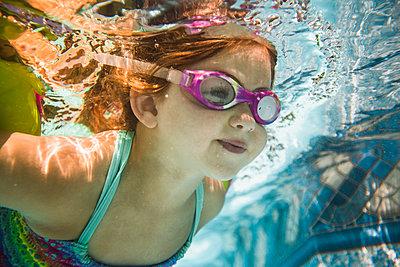 Caucasian girl swimming underwater in swimming pool - p555m1411538 by John Fedele
