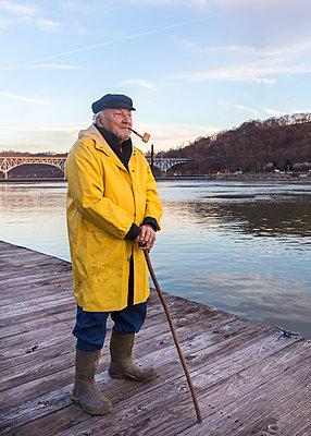 Older Caucasian fisherman standing on dock - p555m1491165 by Tom M Johnson