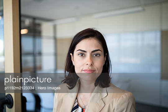 Portrait of businesswoman in modern office - p1192m2123334 by Hero Images