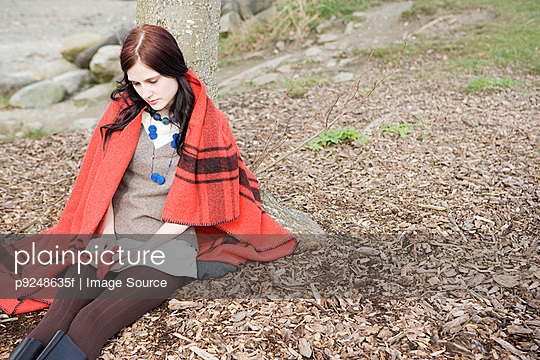 Young woman sitting alone - p9248635f by Image Source