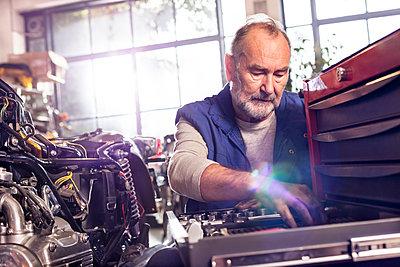 Senior male motorcycle mechanic retrieving tools in toolbox in workshop - p1023m1443962 by Agnieszka Olek