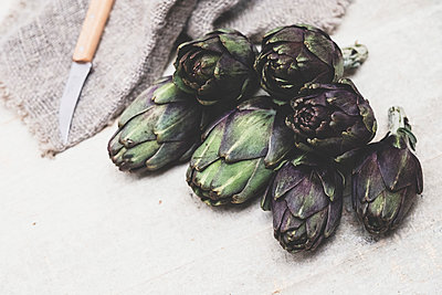 High angle close up of kitchen knife and fresh artichokes on grey background. - p1100m2084871 by Mint Images