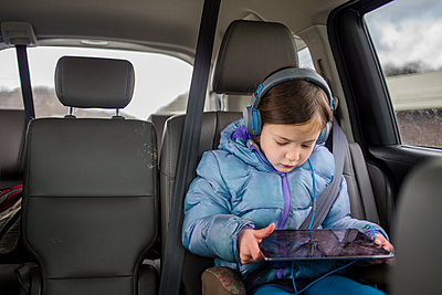 Front view of a small child in a carseat watching a tablet screen - p1166m2136582 by Cavan Images
