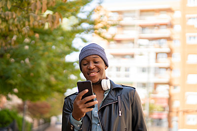 happy young african man in the city listening to music - p1166m2218262 by Cavan Images