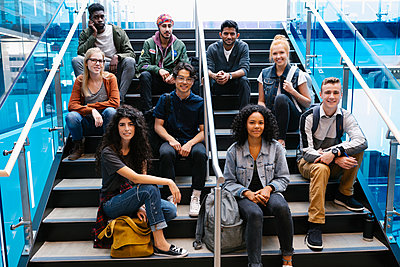 Portrait of university students sitting on staircase and looking at camera - p1192m2110075 by Hero Images