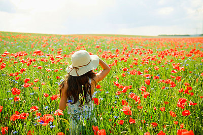 Girl walking in sunny, rural red poppy field - p301m2075907 by Sven Hagolani
