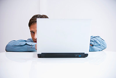 businessman hiding behind laptop computer - p3164302f by beyond