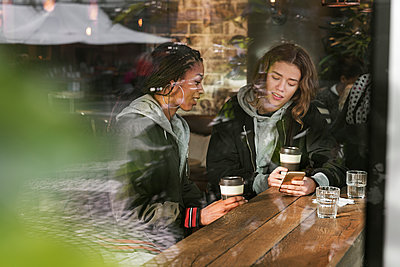 Teenage girls in cafe - p352m2121197 by Folio Images