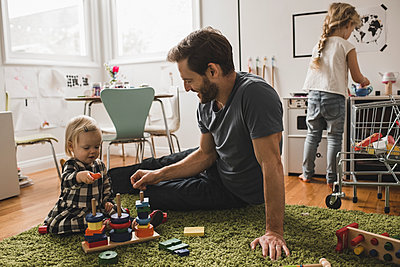 Father and daughters playing with toys in playroom at home - p426m1451760 by Maskot