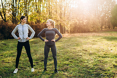 Two girlfriends are doing exercises in nature, looking at each other. - p1166m2171850 by Cavan Images