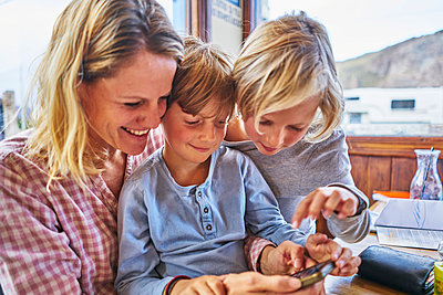 Happy mother with two sons sitting at table in a cafe playing with cell phone - p300m2069417 von Stefan Schütz