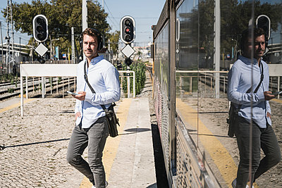 Young man with headphones and smartphone leaving train - p300m2156719 by Uwe Umstätter