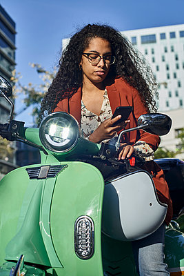 Young woman text messaging on smart phone in city during sunny day - p300m2226757 by Veam