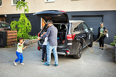 Father playing with children while mother rolling electric charger by car - p426m1192977 by Maskot