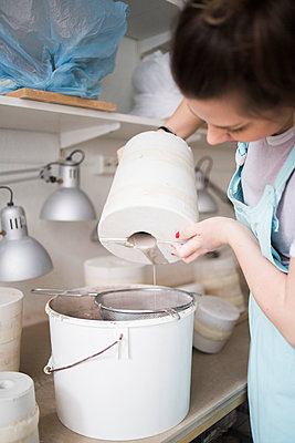 Young female potter pouring clay from vase in colander over bucket at workshop - p426m1451634 by Maskot