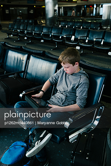 Boy Playing iPad in Airport - p1262m1440861 by Maryanne Gobble