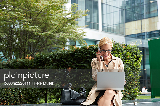 Businesswoman talking on mobile phone while working on laptop at office park - p300m2226411 by Pete Muller