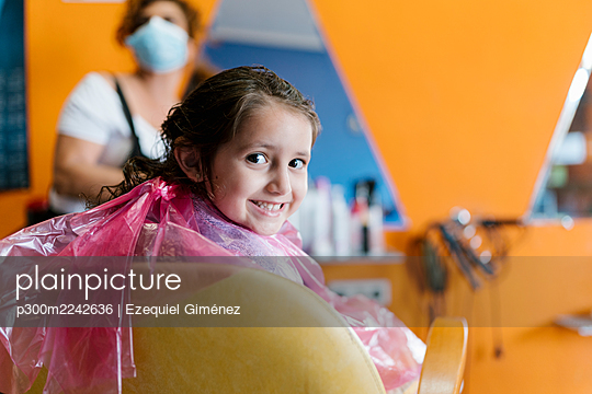 Smiling cute girl wearing pink apron with hairdresser in barber shop - p300m2242636 by Ezequiel Giménez