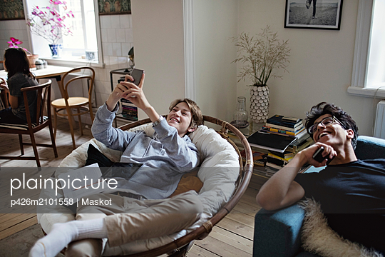 Smiling teenage boy taking selfie while studying with friend in living room at home - p426m2101558 by Maskot