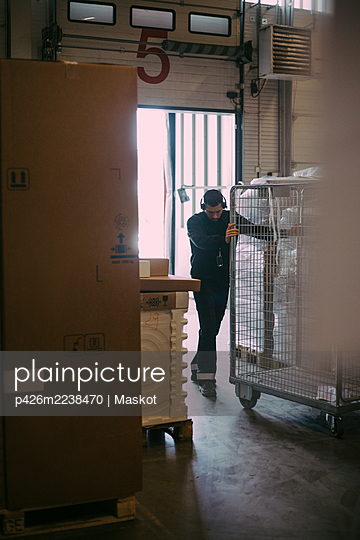 Male manual worker pushing cage trolley at warehouse - p426m2238470 by Maskot