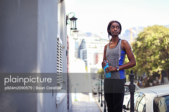 Young female runner sitting on city sidewalk looking over her shoulder - p924m2090579 by Bean Creative