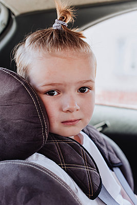 Little boy 5 years old in a child safety seat sitting patiently in the back of a car - p1166m2280906 by Cavan Images
