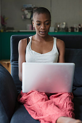 Young woman using laptop on sofa at home - p301m961104f by Halfdark