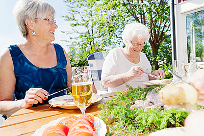 Senior women eating at table in garden - p312m1551947 by Johner Images