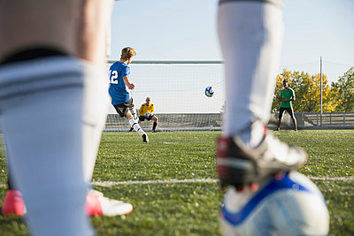 View through legs of soccer player kicking ball. - p328m840833f by Hero Images