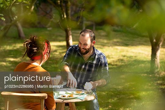 Happy couple enjoying cake at summer garden table - p1023m2286985 by Martin Barraud