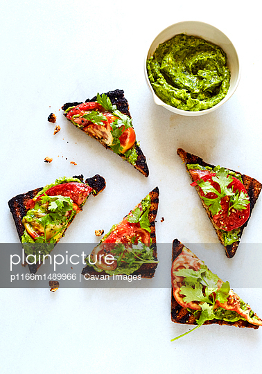 Overhead view of open faced sandwiches and chutney over white background - p1166m1489966 by Cavan Images