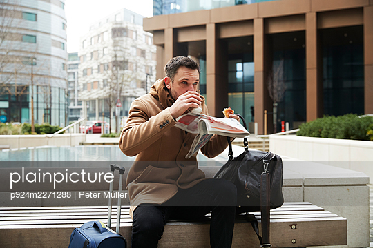 UK, London, Man eating breakfast on bench - p924m2271288 by Peter Muller