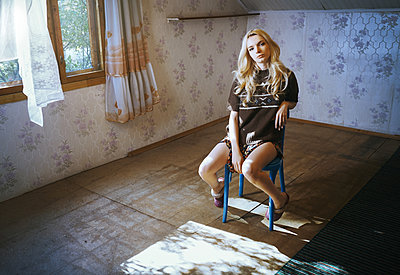 Blond woman sitting on the wooden chair at her rural house - p1577m2220128 by zhenikeyev