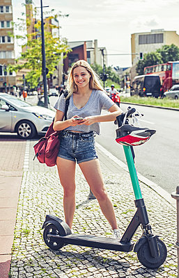 Portrait of smiling young woman with E-Scooter in the city, Berlin, Germany - p300m2140193 by Bernd Friedel
