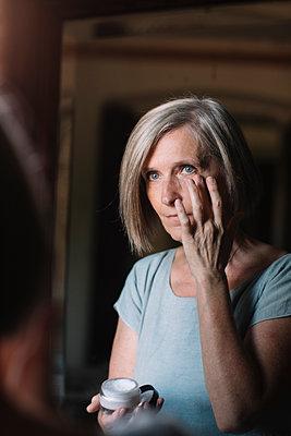 Mature woman applying face cream around eye at home - p300m2281443 by Alberto Bogo