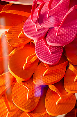 Full frame shot of pink and orange flip-flops seen through glass at store - p301m1148223 by Etienne Girardet