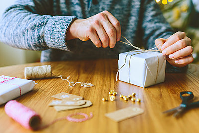 Finland, Man wrapping christmas gifts - p352m1350142 by Eija Huhtikorpi